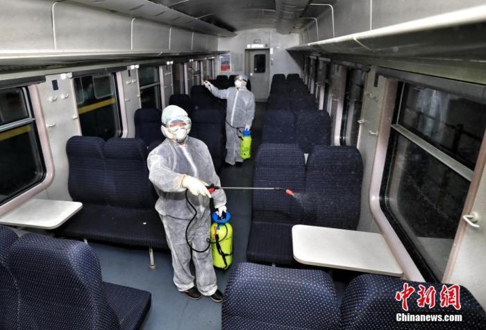2月2日,中國鐵路烏魯木齊局集團有限公司疾控中心消殺科站車消殺隊對車體內對坐席噴灑消毒液。中新社發 擺風亮 攝