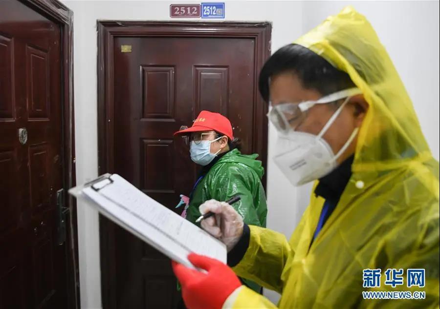 武汉市青山区工人村街道青和居社区网格员李文丽(左)在上门排查(2月18日摄)。新华社记者 程敏 摄