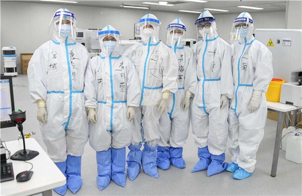 """武汉雷神山医院医学检验科值班人员合影(3月4日摄)。在武汉雷神山医院里,有一群""""侦察兵"""",他们就是医院的检验团队,团队成员中,女性占了半壁江山。新华社记者 程敏 摄"""
