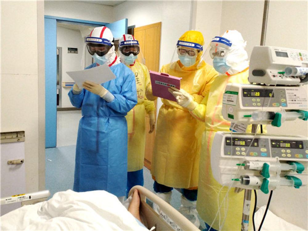 在武汉同济医院中法新城院区ICU病房内,来自北京协和医院的医护人员在病床旁查房交班(2月11日摄)。北京协和医院驰援武汉的135人护理团队中,八成是女同志。新华社发