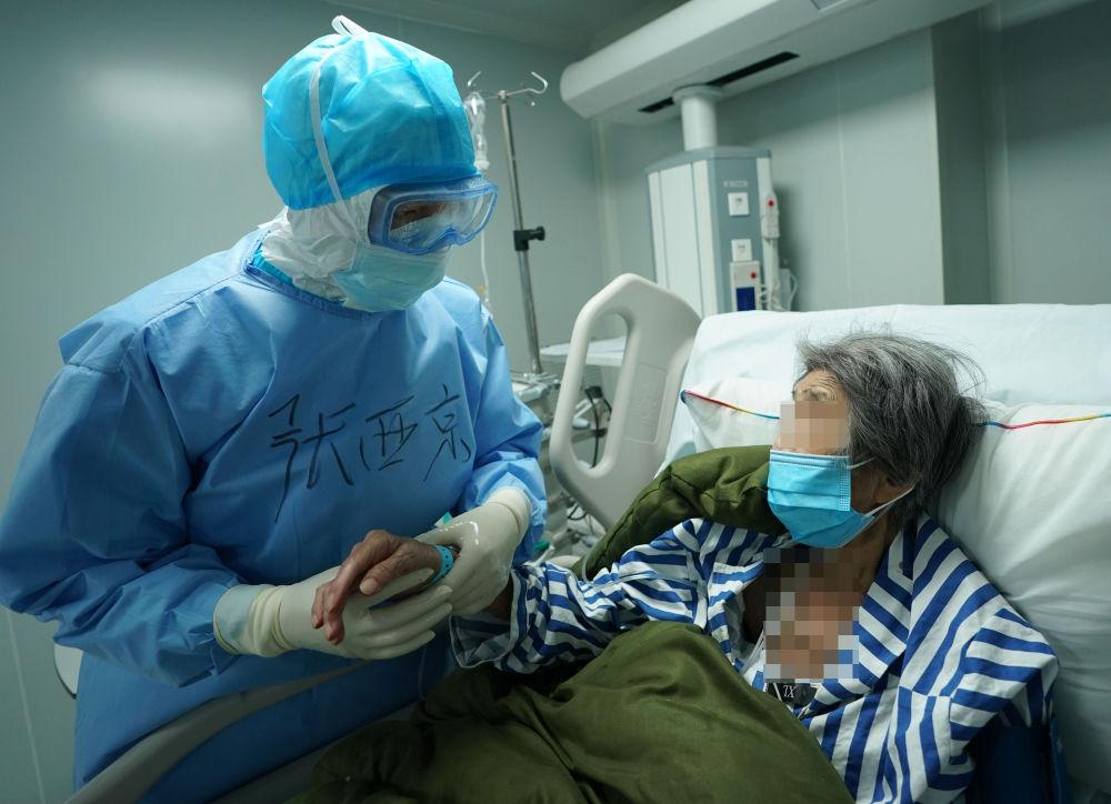 在武汉火神山医院,重症医学一科主任张西京在询问患者的情况(3月17日摄)。新华社记者 王毓国 摄