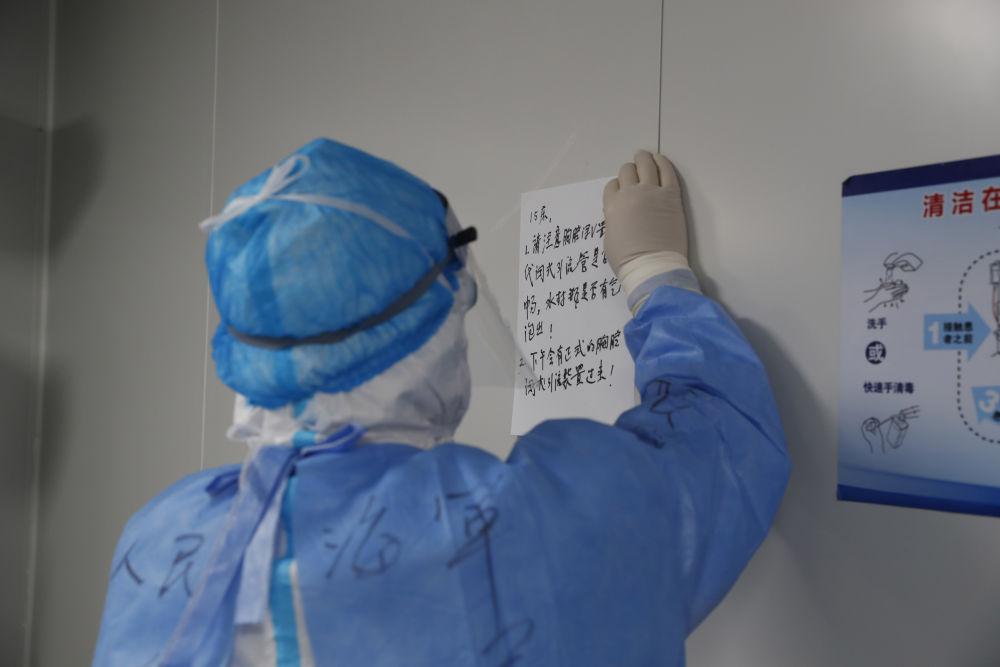 在武汉火神山医院重症监护室内,重症医学一科副主任李文放把写有注意事项的A4纸贴在患者床头(2月24日摄)。新华社发(吴浩宇 摄)