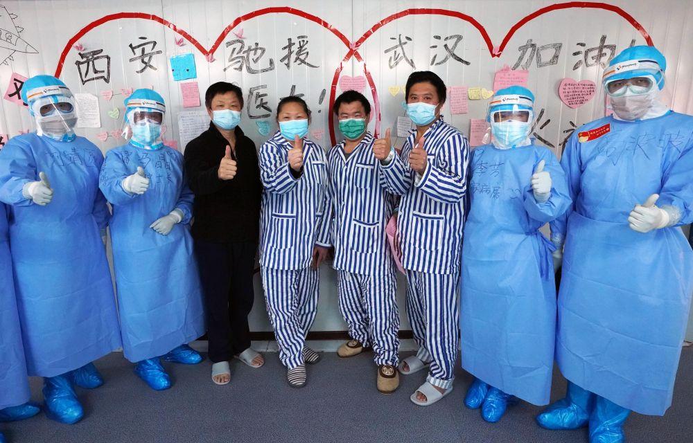 """3月20日,在武汉火神山医院,当日病愈出院的患者在""""心连心许愿墙""""前与医护人员合影留念。新华社记者 王毓国 摄"""