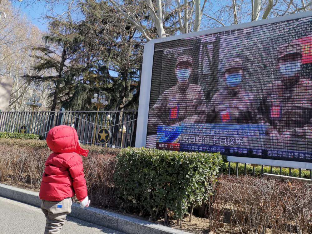 迟象阳的女儿芊芊在大屏幕前看有关妈妈的视频