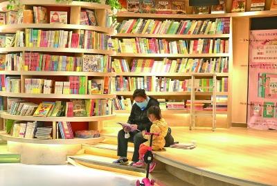 """4月22日,位於北京王府井新華書店三層的""""懷中讀閱童館""""繪本區域,一位媽媽正在給女兒講書。光明日報記者韓寒攝/光明圖片"""