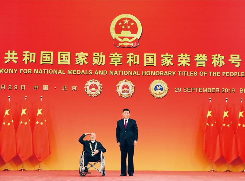 """2019年9月29日,中华人民共和国国家勋章和国家荣誉称号颁授仪式在北京人民大会堂金色大厅隆重举行。中共中央总书记、国家主席、中央军委主席习近平向""""共和国勋章""""获得者张富清颁授勋章。 新华社记者 王晔/摄"""