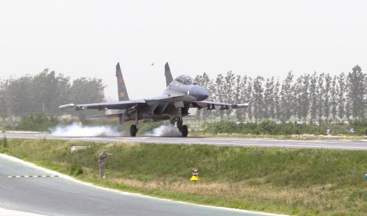 CFP供图  5月25日,济南空军在豫东地区首次组织了多机种高速公路飞机跑道试飞起降。图为我军三代战机着陆成功。   新华社郑州5月25日电 包括第三代战机在内的多种机型25日在郑民高速公路飞机跑道试飞,这在我军历史上还是首次。这次试飞活动进一步检验了跑道技战术性能,并形成了高速公路飞机跑道实战化综合保障能力,为提高飞行部队平战时备降应急能力和军地联合保障部队飞行的协同能力奠定了基础。   据了解,这个跑道是目前全国既有高速公路飞机跑道中设施最全、功能最多、性能最好、净空最彻底的一条,平时可作为民航