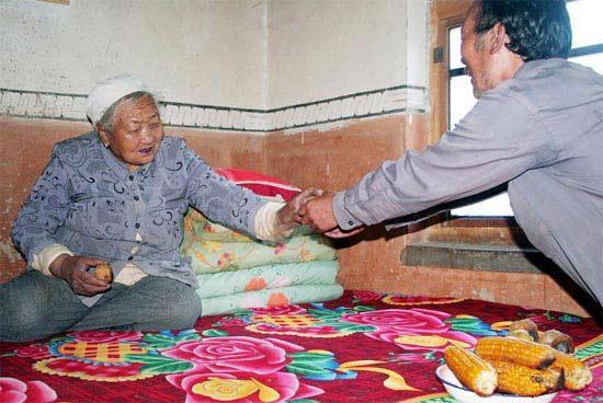 李国峰给母亲递土豆吃。(资料图片)