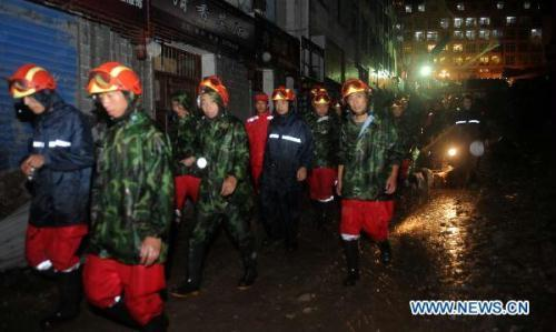Rescuers work in the rain in Zhouqu County, Gannan Tibetan Autonomous Prefecture in northwest China's Gansu Province, Aug. 11, 2010. The death toll in the massive mudslide in Zhouqu has risen to 1,117, with 627 still missing, local authorities said Wednesday. (Xinhua/Nie Jianjiang)