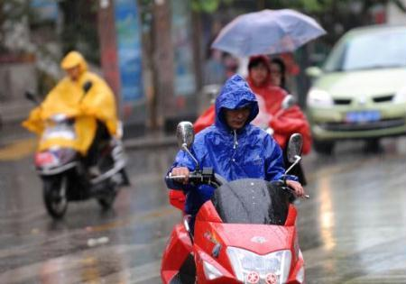 People ride motorcycles in the rain in Kunming, capital of southwest China's Yunnan Province, March 28, 2010. The rainfall brought some relief to parched Yunnan Province on Sunday as a severe drought ravages southwest China.  (Xinhua/Lin Yiguang)