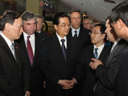 Visiting Chinese President Hu Jintao (C, front) listens to introduction during a tour of the aircraft factory of Bombardier Aerospace in Toronto, Canada, June 26, 2010.(Xinhua/Fan Rujun)