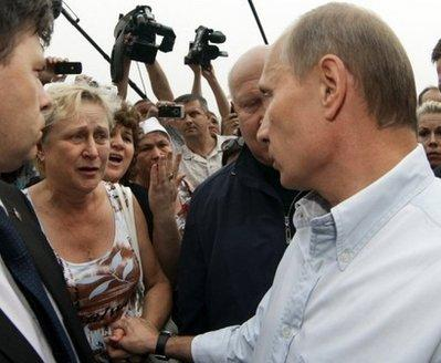 Russian Prime Minister Vladimir Putin (R) speaks with local residents who lost their homes while touring the scene of fire damage near Nizhny Novgorod on July 30. Putin promised on television on Saturday that all the houses would be rebuilt by October, after allocating five billion rubles (165 million dollars).(AFP/RIA/File/Alexey Druzhinin)