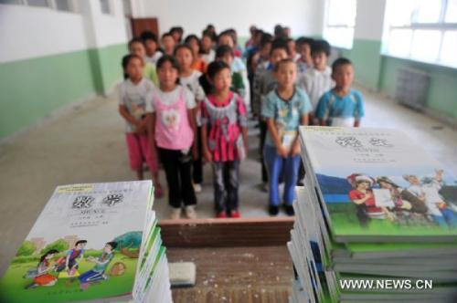 Primary school students line up to get their new textbooks in the landslide-hit Zhouqu County, northwest China's Gansu Province, Aug. 24, 2010. Primary school students in Zhouqu report to their school on Tuesday, the students not only got their new textbooks but also a new school bag filled with stationery and some daily necessities. The schoolbags were prepared by the Ministry of Education and distributed to the students for free. (Xinhua/Liang Qiang)