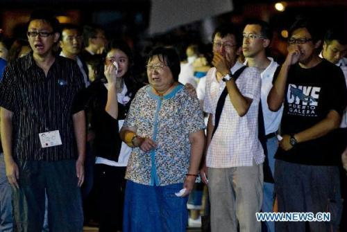 Relatives cry as they see the coffins of victims in Hong Kong, south China, Aug. 25, 2010. The charter plane carrying tourist group members, victims' relatives and the bodies of the eight victims killed in Monday's hostage crisis in the Philippines arrived at Hong Kong Wednesday. (Xinhua/Huang Xiaoyong)