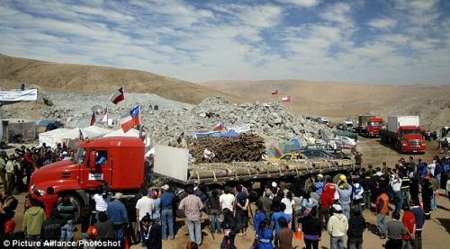 By day: Lorries arrive at the San Jose mine in Copiapo, Chile, with various equipment including a new drilling machine. President Sebastian Pinera today spoke by telephone with some of the 33 men and warned them the rescue mission 'will take some time'