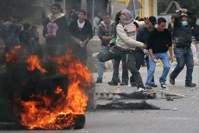 Palestinian youths hurl stones at Israeli troops, not seen, during clashes at the Kalandia checkpoint between the West Bank city of Ramallah and Jerusalem, Tuesday, March 16, 2010. (AP Photo/Majdi Mohammed)