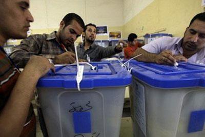 IraqiemployeesoftheelectoralcountingandsortingcenterregistermorevotesinBaghdad.(AFP/Alial-Saadi)