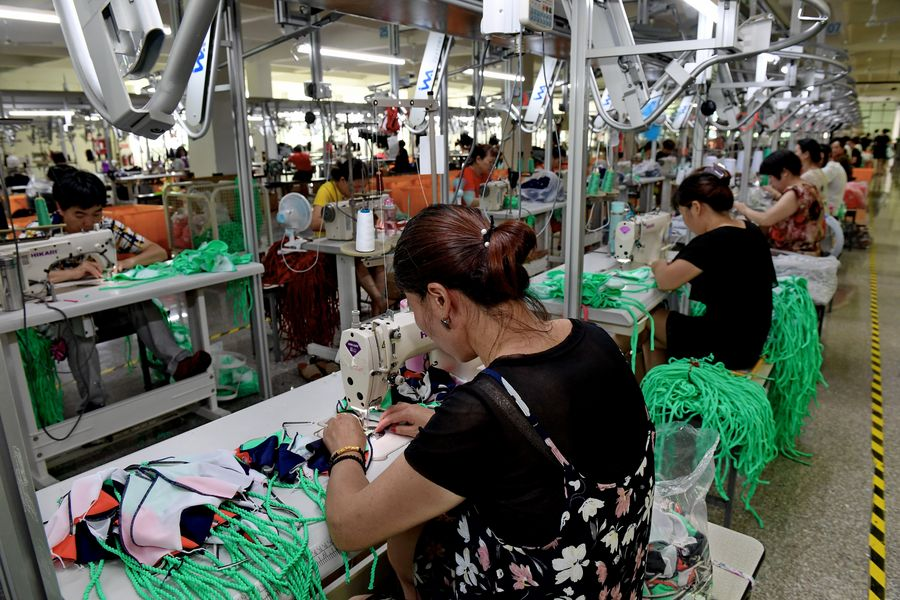 Workers sew swimsuits at a factory of the Qicaihu Garments & Weaving Co., Ltd. in Jinjiang, southeast China