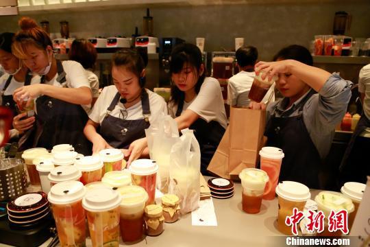 图为店员正在取餐处把饮料装袋。 王远 摄