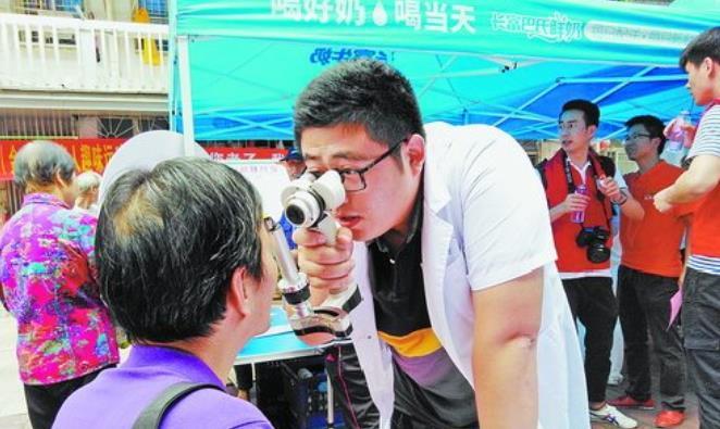 眼科医生为流动人口检查眼健康。