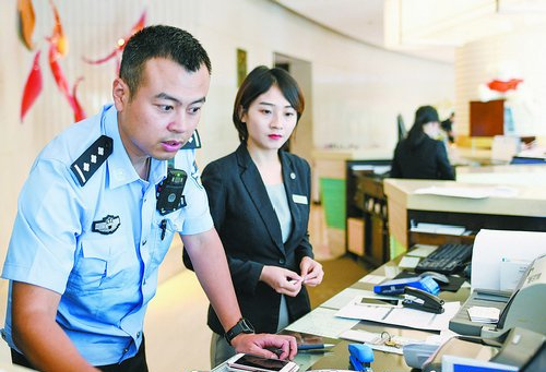 林恒伟(左)在社区酒店开展日常检查。