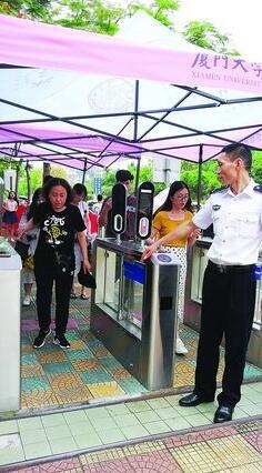 ▲周德新在校门口引导游客进出校园。