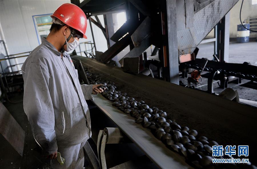 """神木富油能源科技有限公司的工人在对""""型煤""""成品进行巡检(2014年8月14日摄)。 新华社记者 刘潇 摄"""