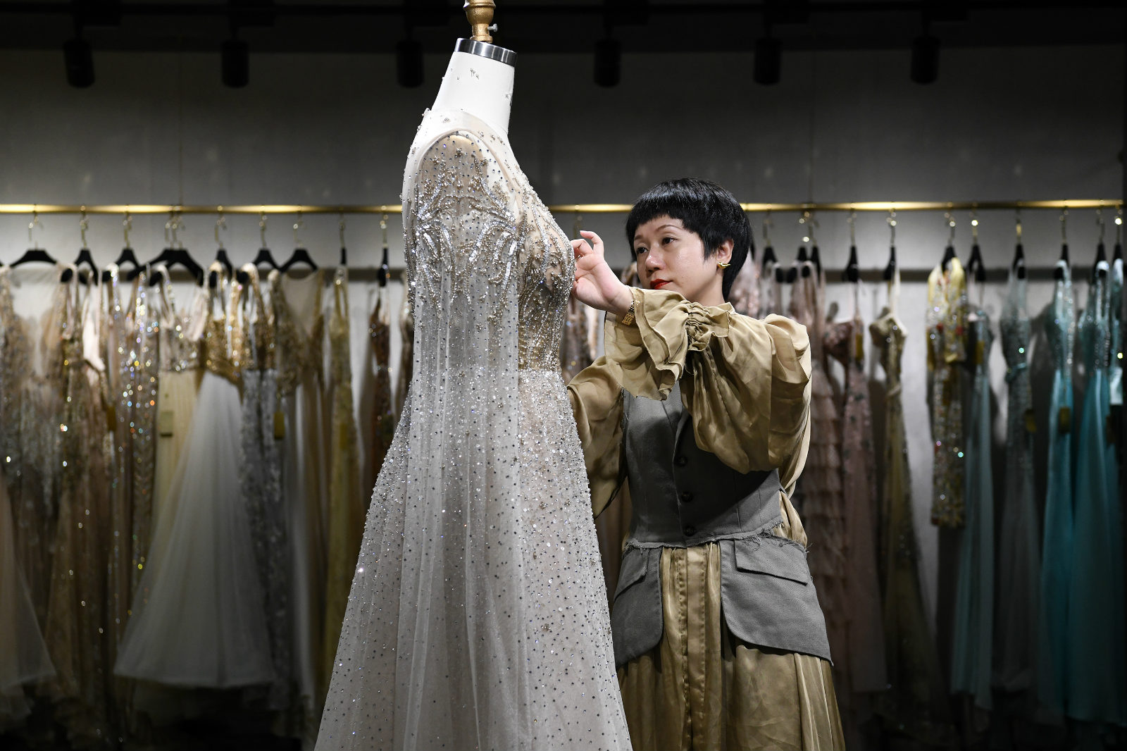 She Keyan, the official heir to the national heritage of Chao Embroidery, settles a wedding dress for display at a showroom for her personal brands in Chaozhou, south China