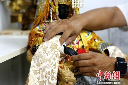8月17日,蔡承哲介绍制作的妈祖神像时说,他的作品和旧时神像最大的不同是,人物手脚关节均可活动,以调整不同造型。中新社记者 杨程晨 摄