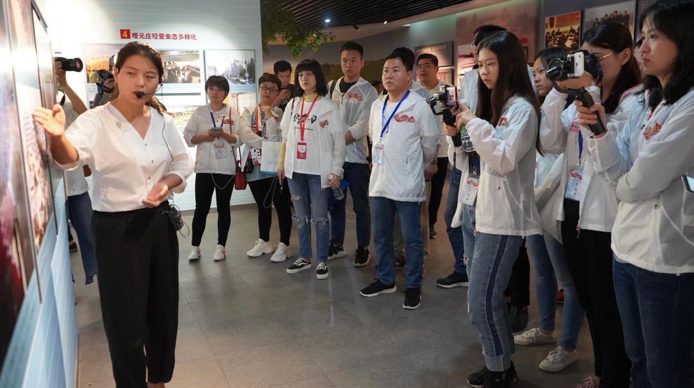 记者们在塔元庄村史馆听讲解员介绍塔元庄的发展