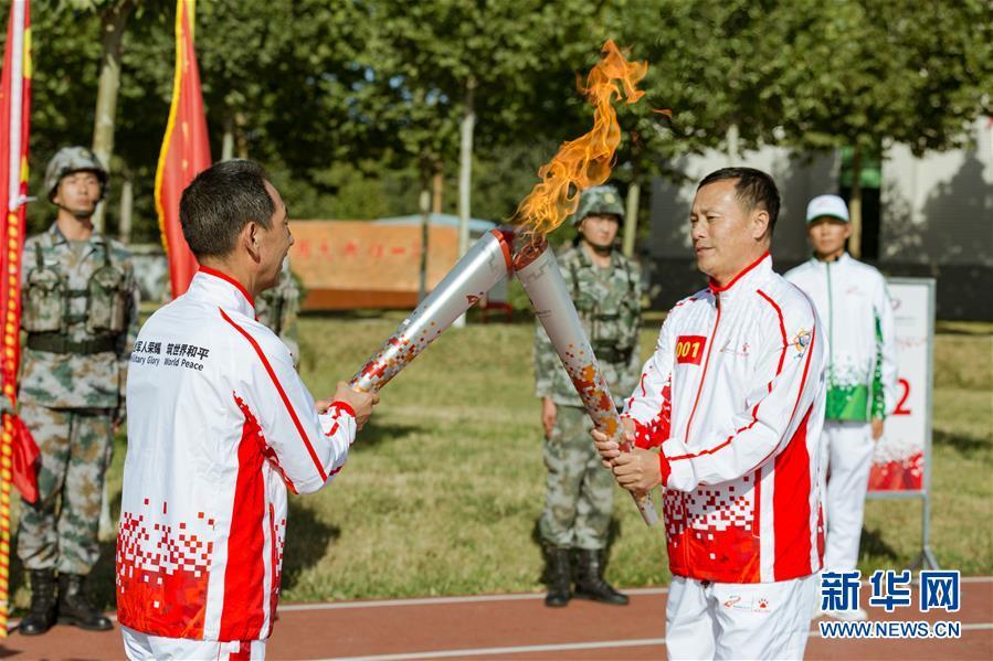 9月23日,第一名火炬手徐洪刚(前右)与第二名火炬手牛先民(前左)在火炬传递活动中交接。新华社发(夏先杰 摄)