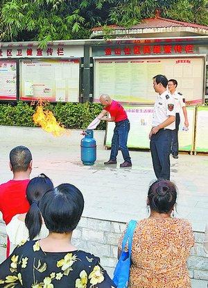 参训人员现场演练液化气瓶灭火操作。