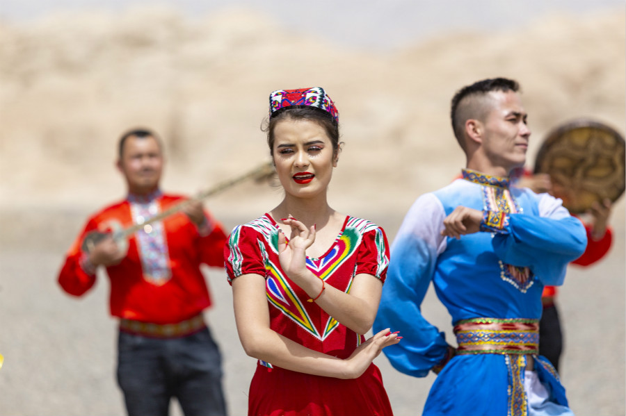 Dancers hold a live broadcast while performing local folk dances at cultural heritage sites in Kucha of Aksu Prefecture, northwest China