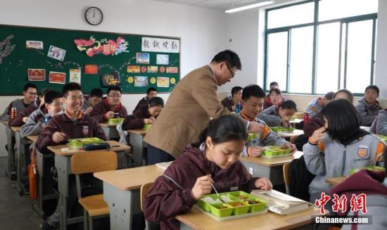 资料图:校长走进教室与学生一起吃中饭。葛勇 摄